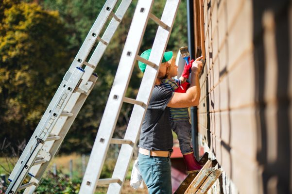 A father and toddler boy outdoors in summer, painting wooden house.