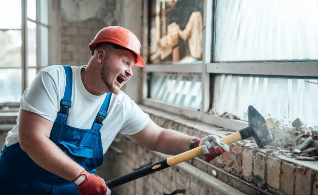 Builder at the construction site, smashing walls with a hammer, screaming