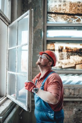 Builder working with a window at a construction site