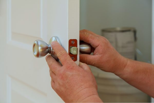Closeup of a professional locksmith installing or repairing a new deadbolt lock on a house door with