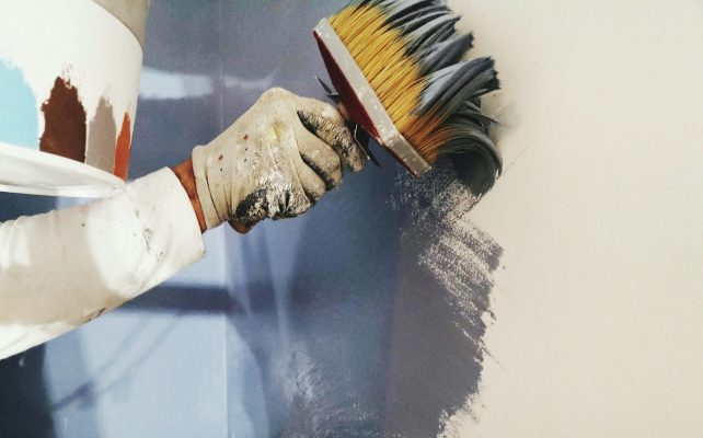 Painting a wall with brushes