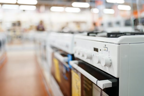 Row of new gas stoves in electronics store, nobody