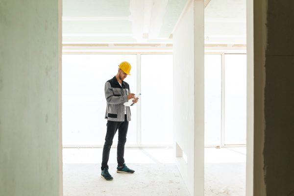 Young engineer in work clothes and yellow hardhat working with p