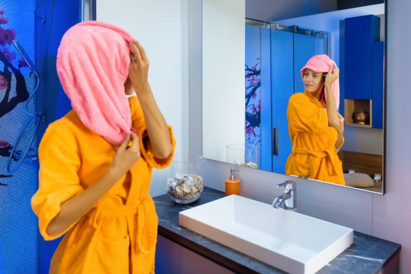 Young woman in bright bathrobe in the bathroom